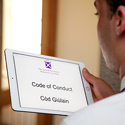 Young man reading the Code of Conduct on a tablet