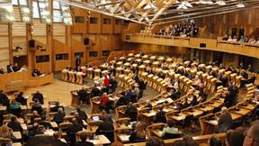 This image shows the chamber full of MSPs during a parliamentary discussion from the perspective of the onlookers